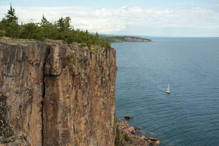 Yemaya sailing past Palisade Head on Lake Superior. Photo by Nate Ptacek